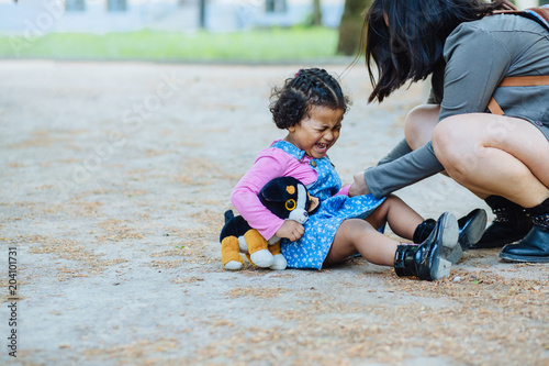 Fotografia Disconsolate hispanic toddler girl three years old crying while sit on the ground outdoor
