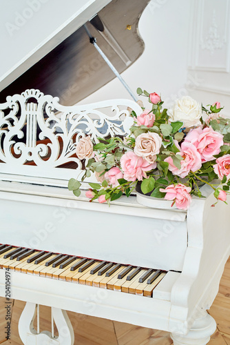 White grand piano with rose flowers in white classic ...