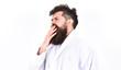 Tired guy in bathrobe yawning. Sleepy man getting up in the morning. Side view hipster over white background