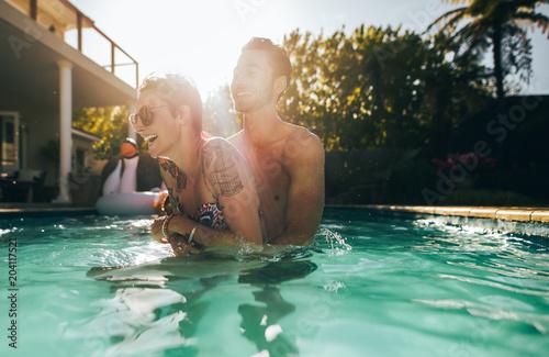 Papiers peints Fluvial Playful couple enjoying in swimming pool