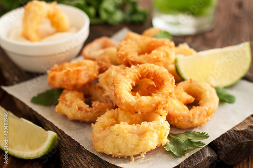 Fried calamari rings on wooden cutting board