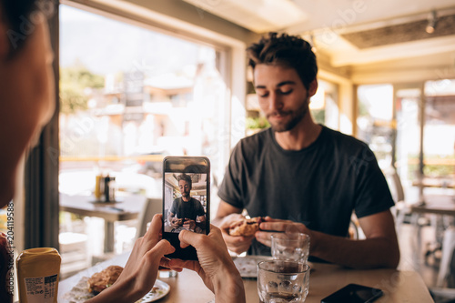 Photo  Woman capturing pictures of man eating burger