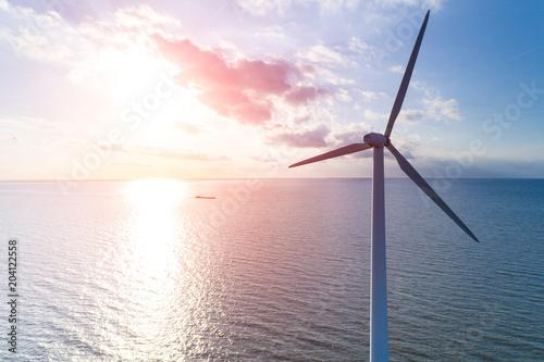Obraz na plátně  Sunset above the windmill in the ocean
