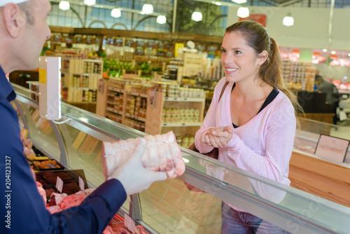 Foto op Plexiglas Bakkerij Lady buying joint of meat