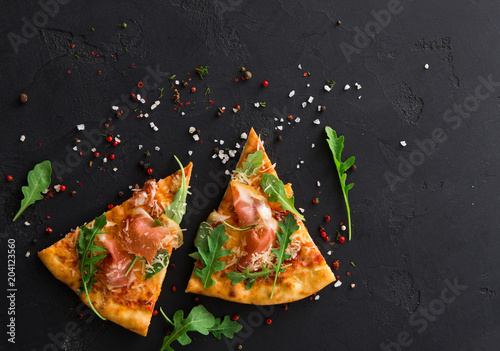 Pizza with prosciutto and rocket salad copy space