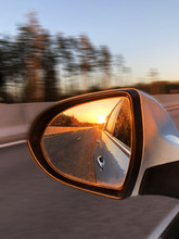 Sunset Light In A Rear View Car Mirror. Car On A Way To The Sea. Sunset Scene Reflection In The Mirror Of Car. Car Detailing