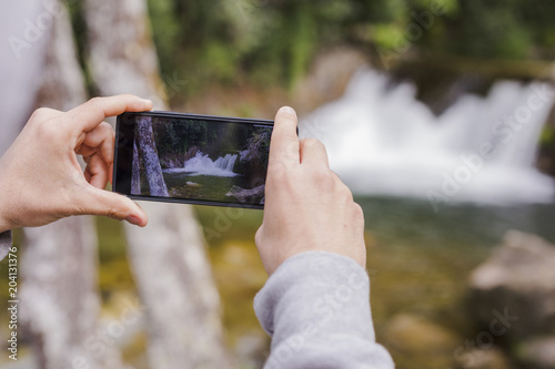 man hands taking a picture with mobile phone of a cascade in nature. Sunny weather. Lifestyle and Travel concept