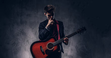 Handsome Young Thoughtful Musician With Stylish Hair In Elegant Clothes Posing With A Guitar In His Hands.