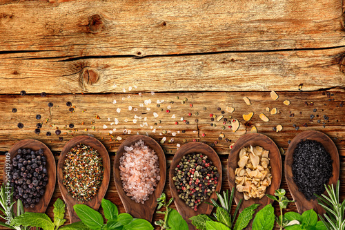 Foto op Canvas Kruiderij Various colorful herbs and spices on wooden table