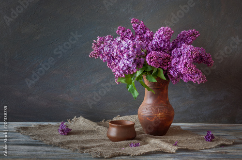 Fototapeta Still Life in a rustic style: A bouquet of lilac and pottery on a wooden table. obraz