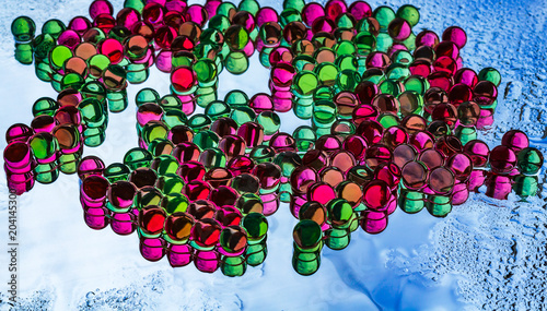 A beautiful horizontal texture of a group of multi-colored transparent hydrogel balls with reflections