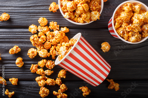 Sweet caramel popcorn in paper cups close-up on the table. horizontal top view