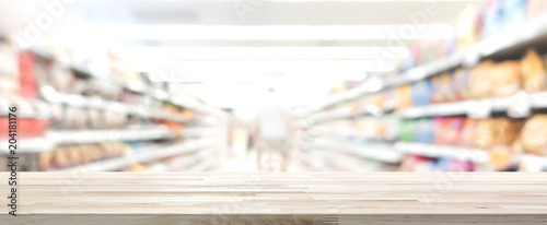 Wood table top with blur supermarket in background, panoramic banner