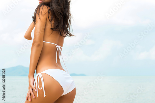 Beautiful shape woman in white bikini swimsuit posing at the beach