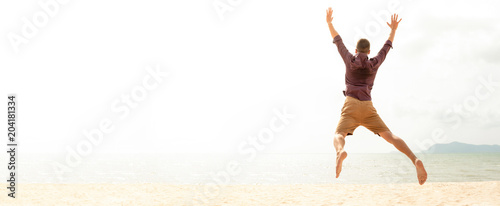 Photo  Energetic happy man jumping at the beach on summer holidays