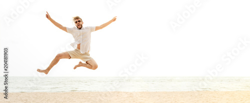 Fotografia  Young energetic happy tourist man jumping at the beach