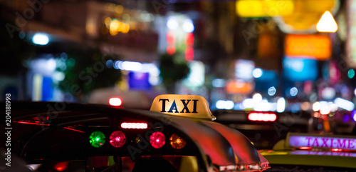 Tuk-Tuk Taxi sign with defocused lights blur in Chinatown in Bangkok at night , Thailand , Southeast asia .