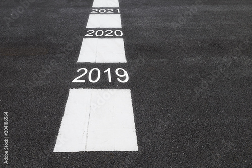 Fotografia  Number of 2019 to 2021 on asphalt road surface with marking lines, happy new yea