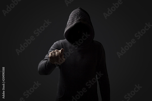 Photographie Faceless man in a hood with points a finger at the viewer on a dark background