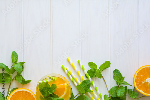 Orange lemonade with slices of orange, ice and mint on white wooden background. Top view. Copy space