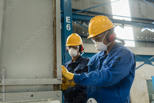 Cuadros en Lienzo Two blue-collar workers wearing protective equipment while insulating an industr