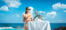 Woman In Golden Dress Having Food At Beach Party With Pool And Beach In The Background