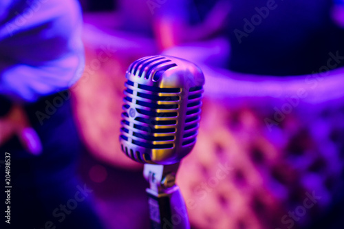 Fotografija  microphone on stand up comedy stage with reflectors ray, high contrast image