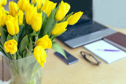 Large beautiful bouquet of yellow tulips on a desk in the office. Congratulations on the holiday or birthday. Flowers as a gift.