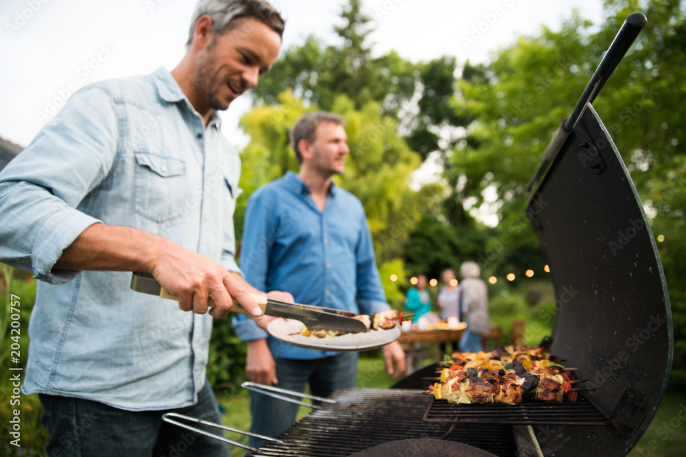 Fototapety, obrazy: in a summer evening,  two men  in their forties prepares a barbecue for  friends gathered around a table in the garden