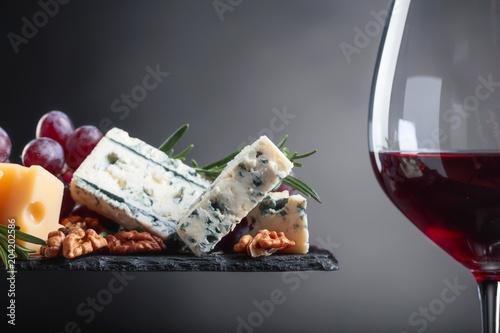 Plakat Kieliszek czerwonego wina z różnych serów.