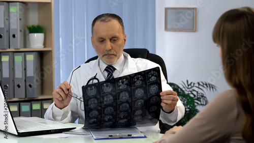 Fototapeta Neurosurgeon observing brain x-ray, going to tell patient about serious illness