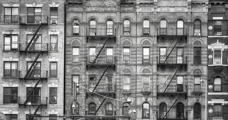 Fototapeta Black and white picture of old buildings with fire escapes, one of the New York City symbols, USA.