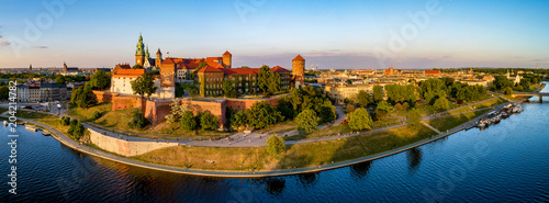 obraz PCV Krakow, Poland. Wide aerial panorama at sunset with Royal Wawel castle and cathedral. Far view of old city and old Jewish Kazimierz district. Vistula river bank, park, promenade and walking people