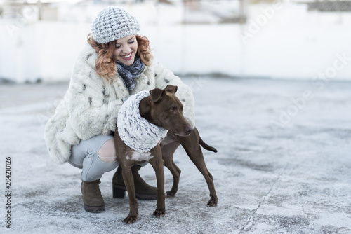 Happy womn playing in winter with her dog. Jaen, Spain.