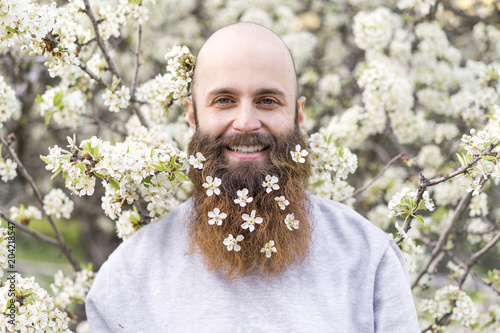 Portrait of laughing hipster with white tree blossoms in his beard
