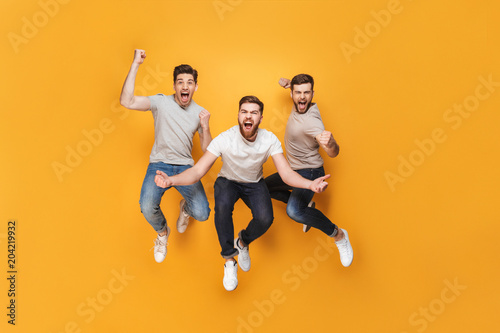 Three young happy men jumping together