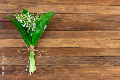 Lily of the valley flower bouquet tied with twine on wooden retro grunge background with copy space