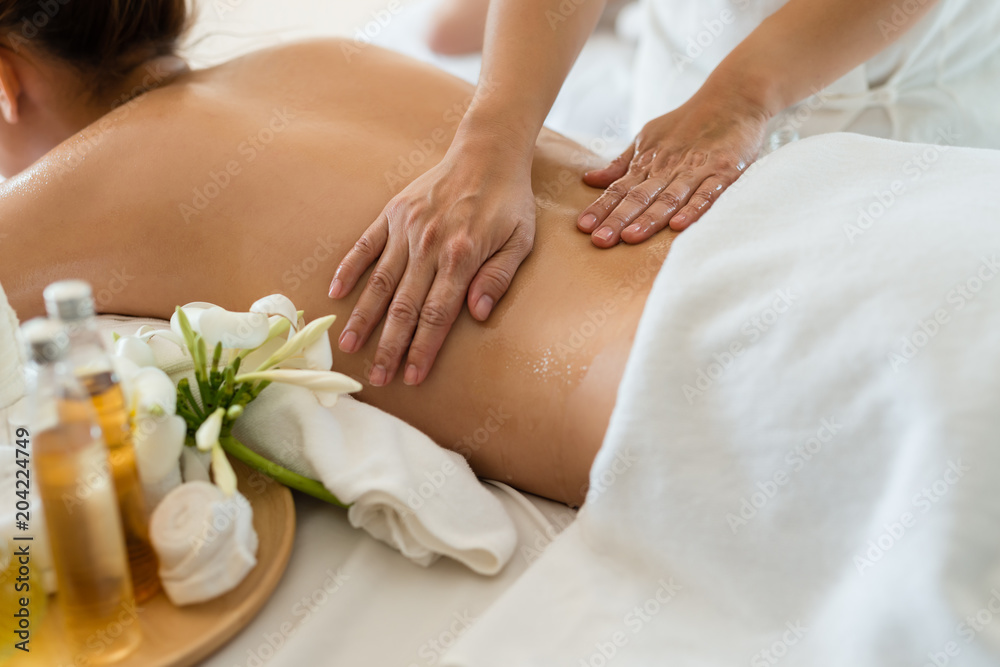 Fototapeta Young beautiful Asian woman sleep relaxing in the Oil spa massage in salon. Select focus hand of masseuse