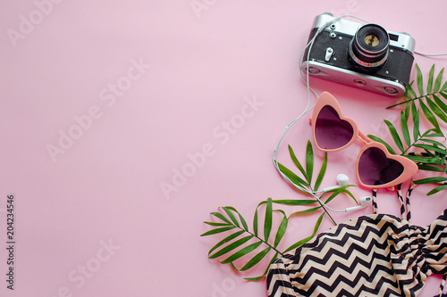 Papiers peints Magasin de musique summer vacation concept. stylish pink sunglasses, modern swimsuit, photo camera,headphones and green palm leaves on pink background, flat lay. space for text. time to travel