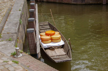 Little Boat With Stacked Gouda Cheeses In A Canal.