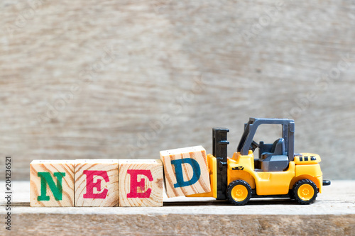Fotografie, Obraz  Toy forklift hold letter block D to complete word need on wood background