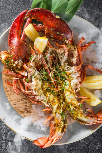 Grilled lobster with lemon baked in Josper oven. Served on the plate with dry ice