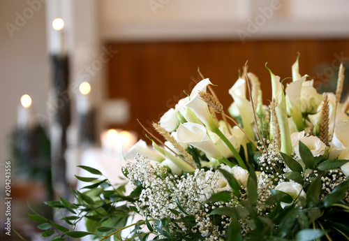flowers on an altar in the church and the candles on background - 204243556
