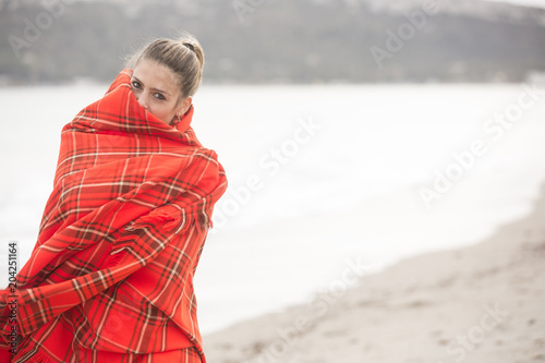 Fotografía  Bella ragazza bionda si copre con una coperta a quadri rossa - sfondo spiaggia e