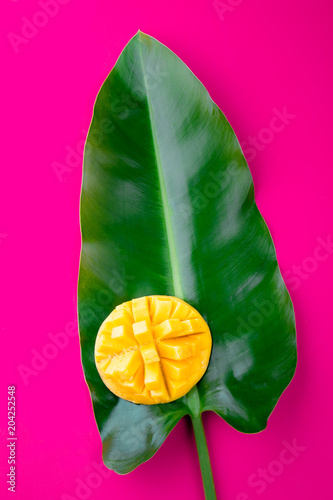 Staande foto Roze Creative layout made of summer tropical fruits mango and tropical leaves on pink background. Flat lay. Tropical food concept.