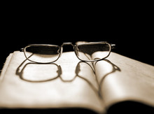 Glasses Lying On A Book With A Shadow In The Shape Of A Heart