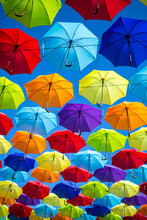 Colorful Umbrellas Background. Coloruful Umbrellas Urban Street Decoration. Hanging Multicoloured Umbrellas Over Blue Sky. Umbrellas With Many Colours.