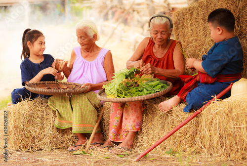 Fotografía  Traditional Asian Thai rural daily life, grandchildren in cultural costumes help their seniors preparing local food ingredients for the meal