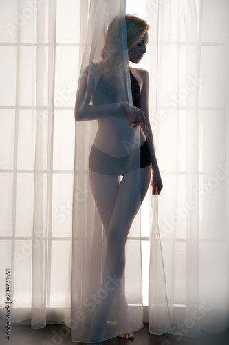 Tuinposter womenART Sensual blonde at the window