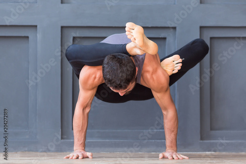 Man doing yoga exercises and practicing handstand balance pose on grey urban background Wallpaper Mural
